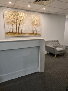 White waiting room with grey chair and golden tree painting